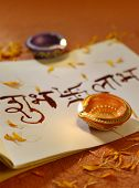 Indian traditional lamps placed on a book with Sanskrit calligraphy