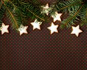 Christmas background with twig of fir tree and cinnamon stars on brown background with dots
