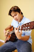 stock photo of acoustic guitar  - A young man playing guitar - JPG