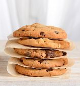 Closeup of a stack of fresh baked cookies Chocolate Chip, Oatmeal Raisin, White Chocolate Chip cookies on parchment paper. Square format on a rustic white kitchen table.