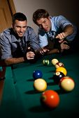 Happy friends discussing a game of billiard at table with beer in hand. Selective focus, pointing. Having fun.