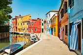 Burano island canal, colorful houses and boats, Italy.