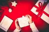 Giftbox in female hands and other Christmas symbols over red background