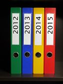 Four color binders organized by year 2012 to 2015 placed on bookshelf