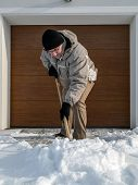stock photo of snow shovel  - Man clearing driveway of snow with shovel after heavy snowing - JPG