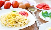 spaghetti dinner with tomatoes, cheese and vegetables close up