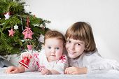 Christmas Portrait Of Little Boy And His Adorable Baby Sister Under Decorated Tree Holding Red Bell