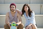 Young couple sitting on concrete steps with a skateboard, looking at the camera
