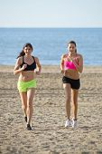 Two women running uphill through the loose sand of of a beach during an endurance workout