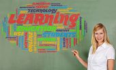 Smiling woman drawing learning and education tag cloud on a chalkboard