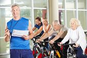 Fitness trainer with senior people on bikes in gym