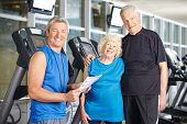 Happy senior couple with personal trainer in fitness center at treadmill
