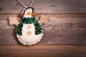 Hand made felt snowman Christmas decoration. Vintage style, over old wood background, with space for