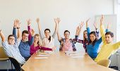 education, teamwork and people concept - group of smiling students raising hands in office