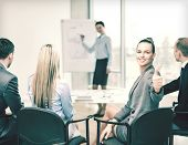 business, office and success concept - smiling businesswoman with team in office showing thumbs up
