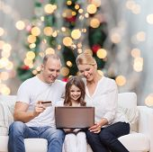 family, holidays, shopping, technology and people concept - happy family with laptop computer and cr