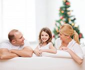 family, childhood, holidays and people - smiling mother, father and little girl over living room and