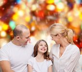 family, childhood, holidays and people - smiling mother, father and little girl over red lights back