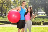 Athletic couple posing in park with fitness equipment