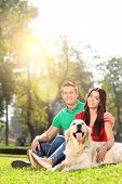 Vertical shot of a couple posing in a park with their dog