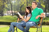 Girl relaxing in a park with her boyfriend seated on a bench