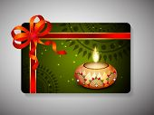 Diwali festival gift card with illuminated oil lit lamp and ribbon decoration on floral decorated green background.
