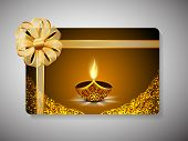 Diwali festival gift card with illuminated lit lamp and ribbon decoration on stylish brown backgroun