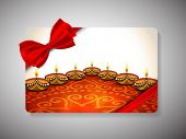 Diwali festival gift card with illuminated lit lamps on floral decorated floor with ribbon bow.