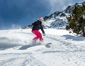Woman Snowboarder In Motion In Mountains