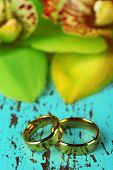 Wedding rings and orchid flowers, close-up, on color wooden background