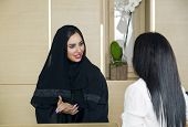 Arabian Receptionist helping a customer on the front desk