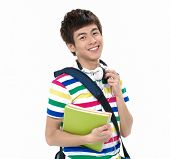 portrait of a smiling school boy holding books with headphones.