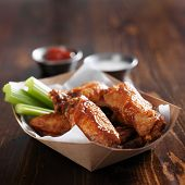 barbecue buffalo chicken wings with celery sticks and ranch sauce in basket