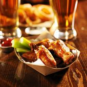 barbecue buffalo chicken wings served with beer, celery, and ranch in basket