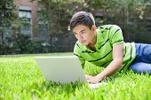 male college student use laptop on the park