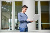 young man standing use laptop at college campus