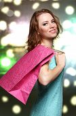 Beautiful young woman with shopping bags on bright background