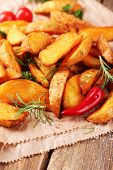 Homemade fried potato with spices and herbs on paper bag, on wooden background