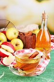 Composition of apple cider with cinnamon sticks, fresh apples on wooden background