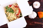 Chinese noodles in takeaway box on bamboo mat background
