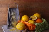 Lemons on napkin in basket, cutting board and grater on wooden background