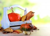 Pumpkins in wooden box and leaves on table on natural background