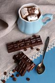 Cup of coffee with marshmallow and chocolate on wooden table