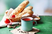 Homemade tomato juice in color mug, bread sticks, spices and fresh tomatoes on wooden table, on brig