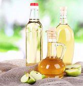 Apple cider vinegar in glass bottles and ripe fresh apples, on wooden table, on nature background