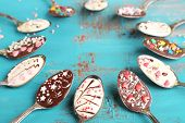 foto of chocolate spoon  - Spoons with tasty chocolate for party on old blue wooden table - JPG