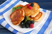 Tasty pancake with fresh berries and mint leaf on plate, on color wooden background