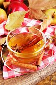 Composition of  apple cider with cinnamon sticks, fresh apples and autumn leaves on wooden backgroun