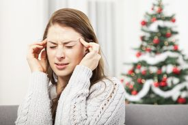 picture of sad christmas  - young unhappy girl has headache from christmas stress with tree in background  - JPG