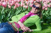 Woman lying in front of pink tulips field